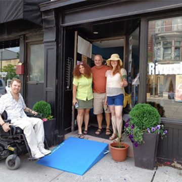 luke out front of a store with a new blue ramp and store staff smiling in the doorway