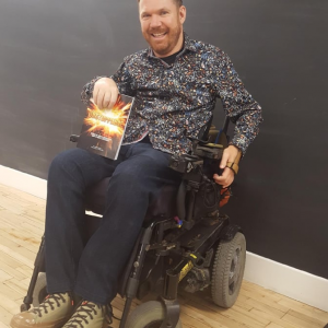 Luke Anderson, smiling and holding up a copy of Unstoppable, the book he co-authored.
