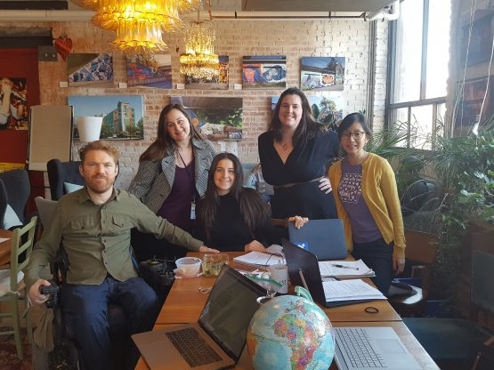 The five members of the StopGap Foundation team in front of an exposed brick wall covered in photos of street art. The team is posed around a table full of laptops, papers, lunch and… a small globe in the lounge of CSI under warmly lit chandeliers. Luke is sporting an uncharacteristically smug smirk, infused with profound undertones of pride. Beside him from left to right are Adrianna, Jessica, Lee-Anne & Debbie, each boasting warm and radiant smiles.