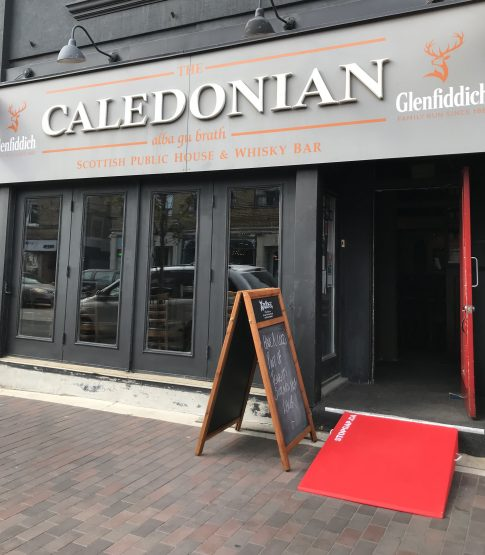 Front entrance to The Caledonian Pub with a bright red rap next to a chalkboard display sign